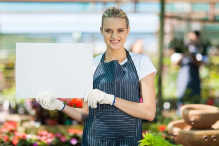 smiling woman in a greenhouse: attractive young female florist holding white board in greenhouse