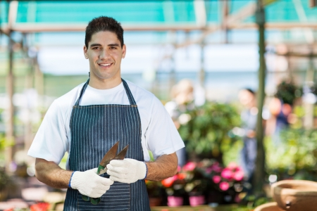 small flowers: handsome young gardener portrait in greenhouse