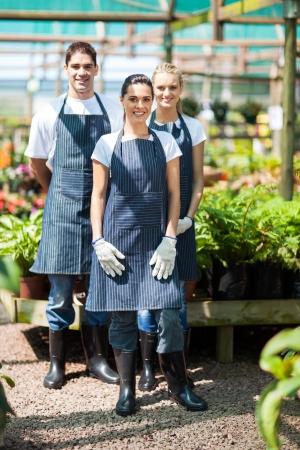 plant nursery: group gardeners portrait in greenhouse