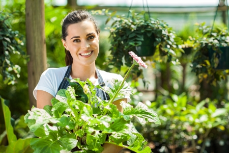 small flower: happy young woman with flowers in nursery