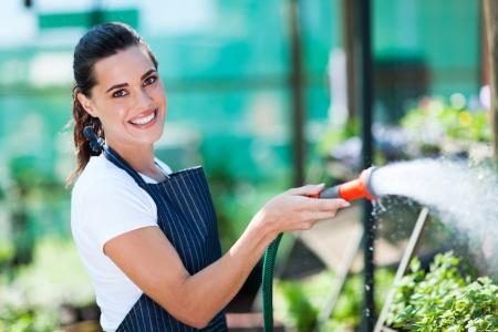 garden hose: pretty florist watering flowers in greenhouse