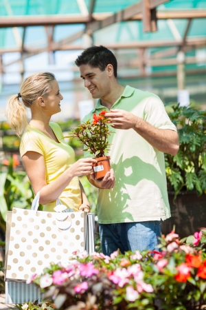 happy young couple shopping for plants in nursery photo