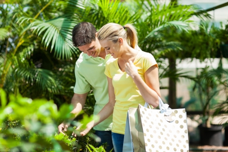 happy young couple shopping for plant in nursery greenhouse photo
