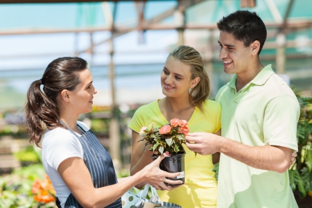 young couple buying flowers in nursery photo