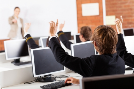 uniform student: group of high school students hands up in computer class Stock Photo