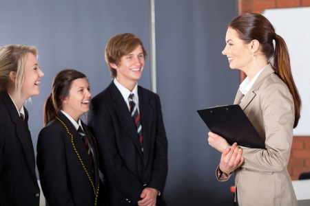 happy high school teacher talking to students in classroom photo