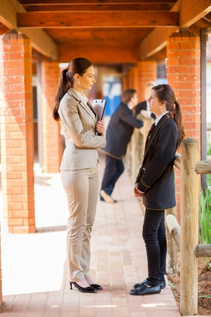 school aged: high school teacher talking to student by school corridor