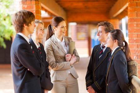 high school teacher: high school teacher talking to students in corridor