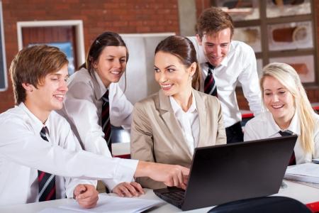 uniforme escolar: profesor de secundaria y estudiantes con ordenador portátil en el aula Foto de archivo