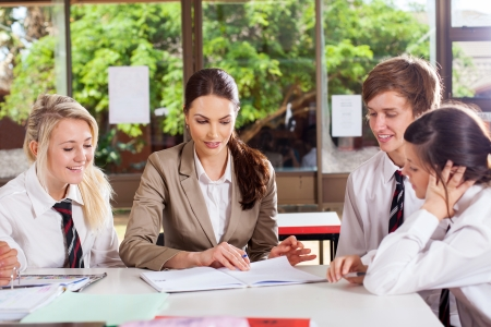 high school teacher helping students in classroom photo
