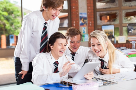 uniform student: group of happy high school students using tablet computer