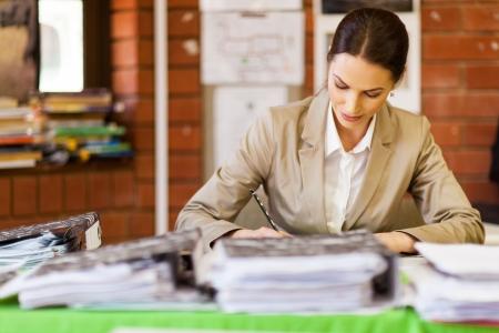 grading: pretty female school teacher working in office