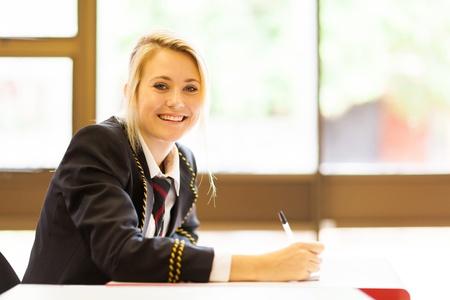 uniform school: ni�a feliz estudiando la secundaria en el aula