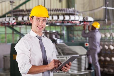 gerente: textil moderna director de la fábrica utilizando equipo Tablet PC