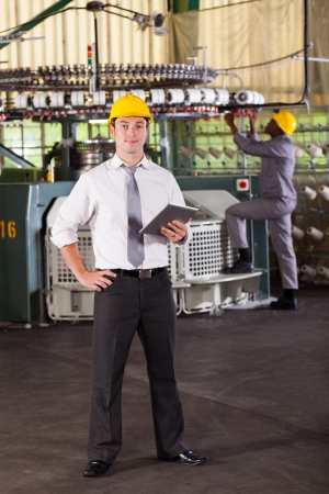 factory worker: portrait of a cloth manufacturing factory manager with tablet computer Stock Photo