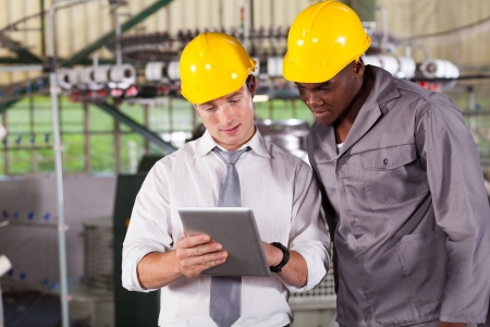 factory manager and worker looking at tablet computer photo