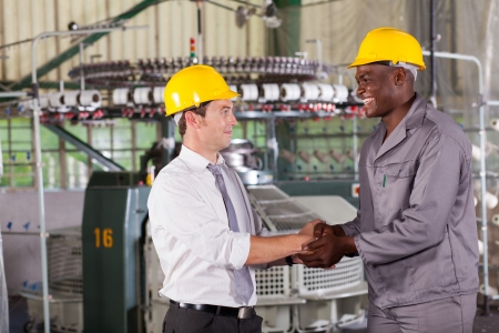 factory manager handshaking with african american worker photo