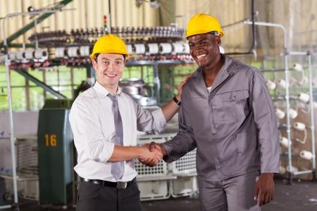 hardworking: boss handshaking and praising hardworking worker in factory