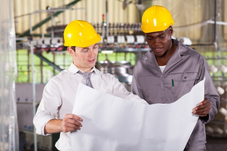 factory manager and worker looking at production plan Stock Photo - 16013883