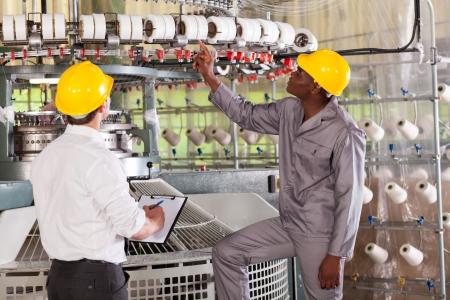 control de calidad: gerente de la fábrica textil y del trabajador de cheques hilo en la máquina de tejer