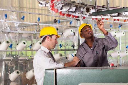 cloth manufacturing: textile factory worker and quality controller checking quality Stock Photo