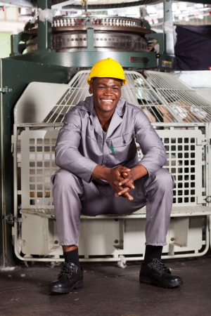 happy african american textile worker sitting on machine photo