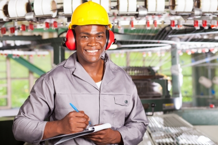 blue collar: handsome african american blue collar worker portrait inside factory Stock Photo