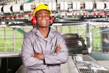 blue collar: happy african american textile worker portrait in front of machinery