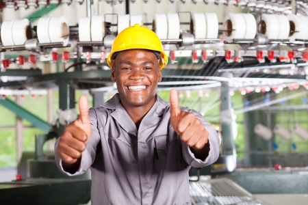 industrial worker: african american textile worker thumbs up in front of weaving loom