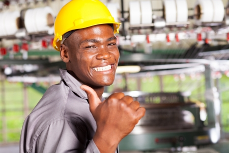 blue helmet: happy african american textile worker thumb up in factory Stock Photo