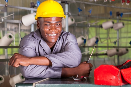 cloth manufacturing: happy african american factory technician repairing loom Stock Photo
