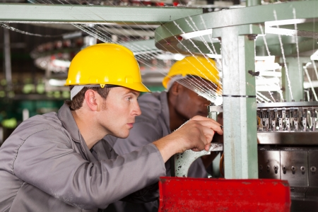 cloth manufacturing: two textile weaving machine mechanics repairing loom Stock Photo