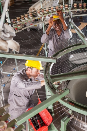 cloth manufacturing: two textile weaving machine mechanics fixing loom