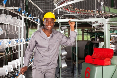 happy african textile factory worker portrait in front of weaving loom photo