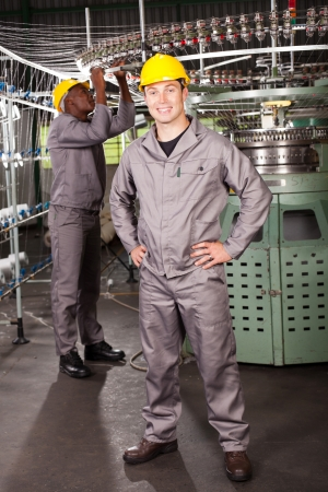 textile factory worker full length portrait in front of machine photo