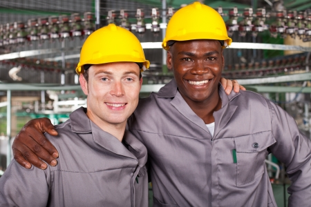 hard worker: two friendly industrial workers colleagues in factory Stock Photo