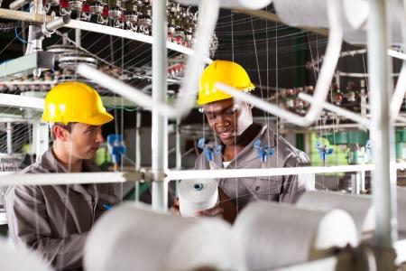 trabajadores: dos obreros textiles en el trabajo Foto de archivo