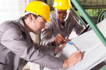 control de calidad: dos obreros textiles tejidos comprobar la calidad en la mesa de control de calidad