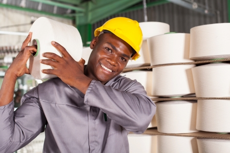 textile factory worker carrying raw material on his shoulder photo
