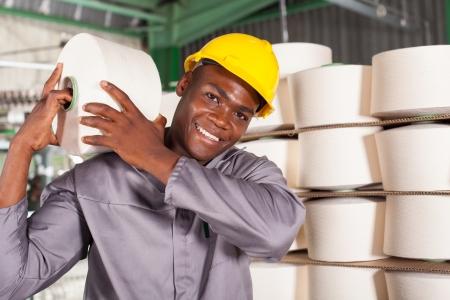 obrero: trabajador de una fábrica textil que lleva la materia prima en el hombro Foto de archivo