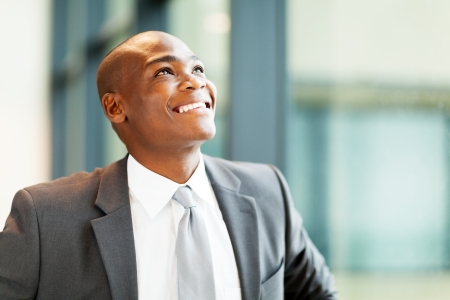 optimistic african american businessman looking up photo