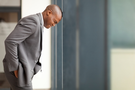 worried executive: stressed african american businessman bang hi head against wall