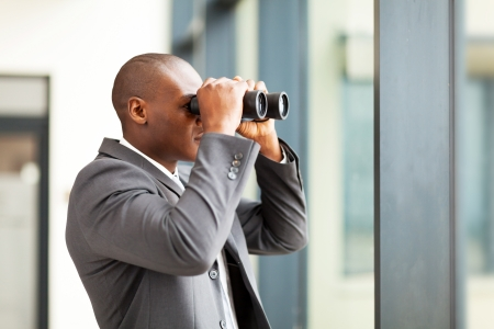 determined african american businessman using binoculars in office photo