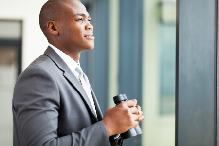determined: determined african american businessman with binoculars