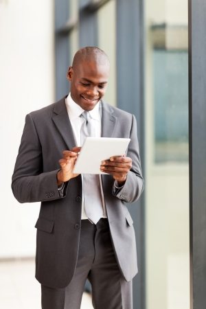 happy african american businessman with tablet computer in office photo