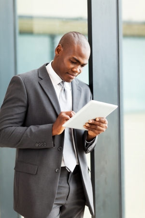 african american male: thoughtful african american businessman with tablet computer in office Stock Photo