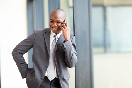 relaxed business man: happy african american businessman talking on mobile phone in modern office