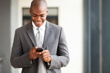 hombres de negro: joven hombre de negocios americano africano de correo electrónico en el teléfono inteligente lectura