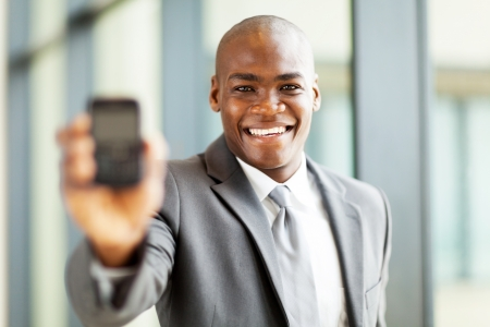 african american businessman holding a smart phone towards the camera photo