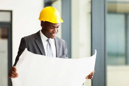 construction manager: happy african american businessman looking at blueprint